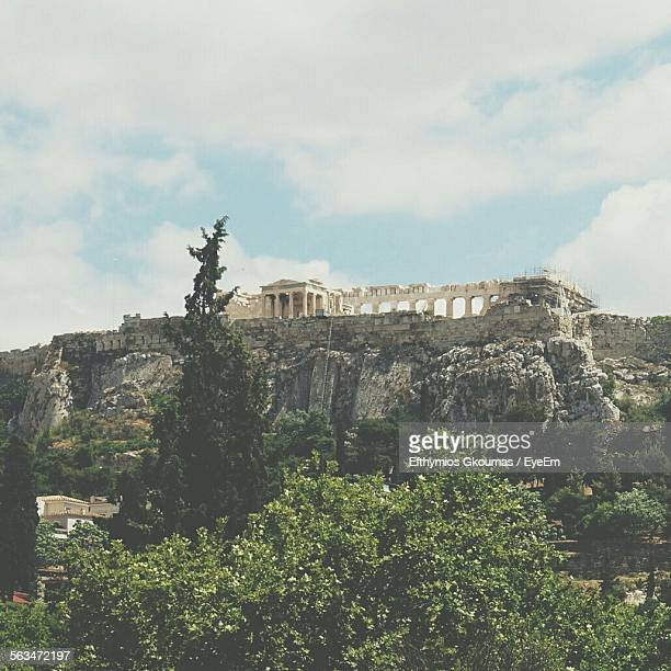 Low Angle View Of Parthenon On Hill Against Cloudy Sky