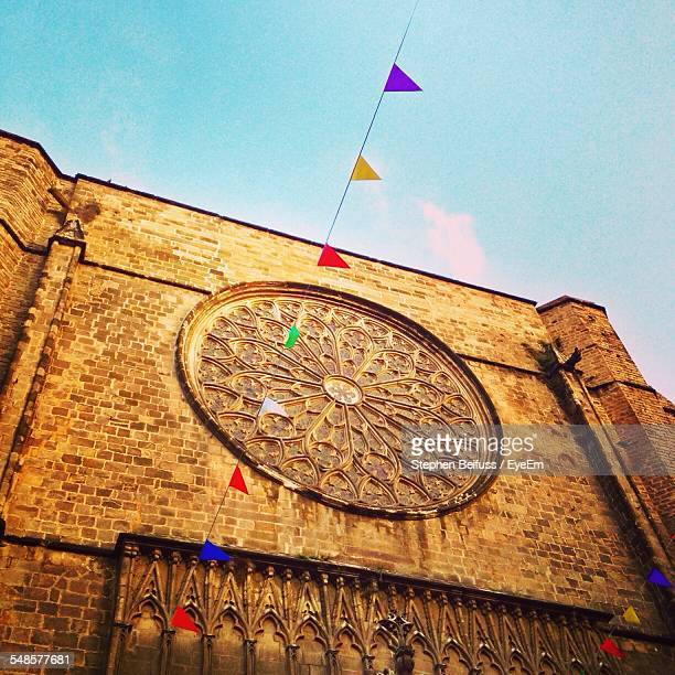 Low Angle View Of Pennant Hanging In Front Of Rose Window