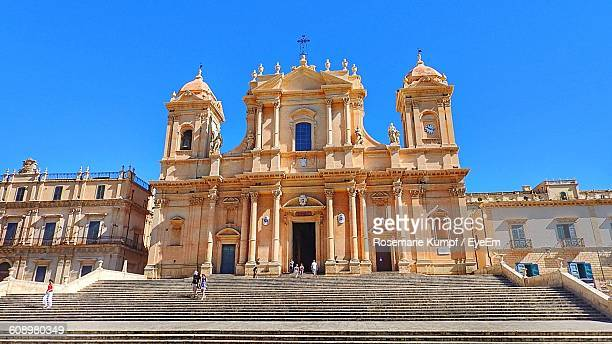 Low Angle View Of People At Noto Cathedral Against Clear Sky