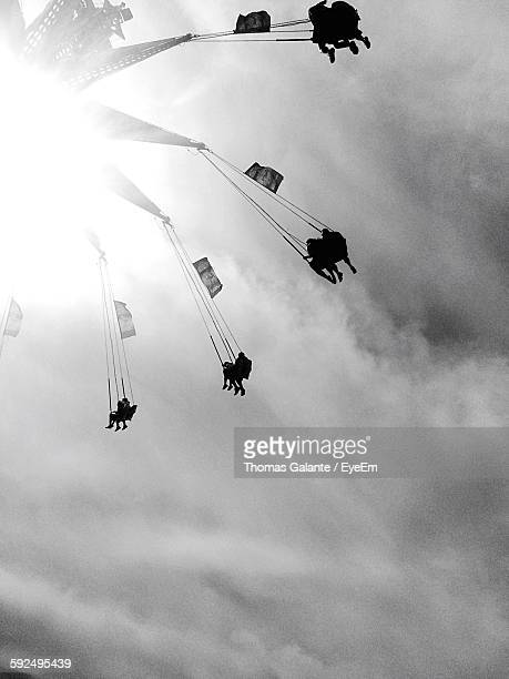 Low Angle View Of People Enjoying Chain Swing Ride Against Cloudy Sky