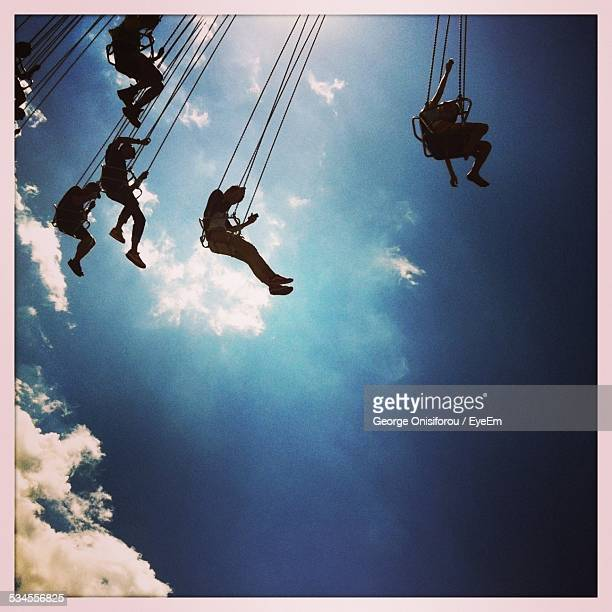 Low Angle View Of People Enjoying Chain Swing Ride Against Sky