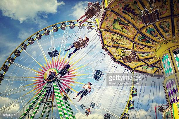 Low angle view of people enjoying on amusement park rides against cloudy sky