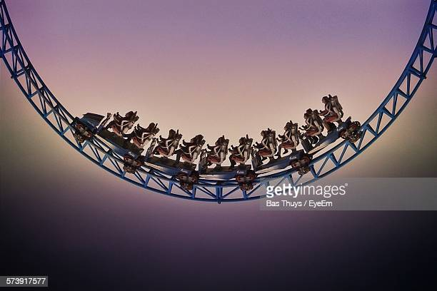 Low Angle View Of People On Roller Coaster Against Sky