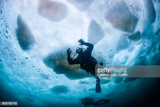 Low Angle View Of People Scuba Diving In Sea During Winter