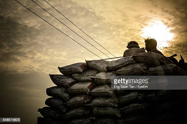 Low Angle View Of People Sitting On Cement Sack