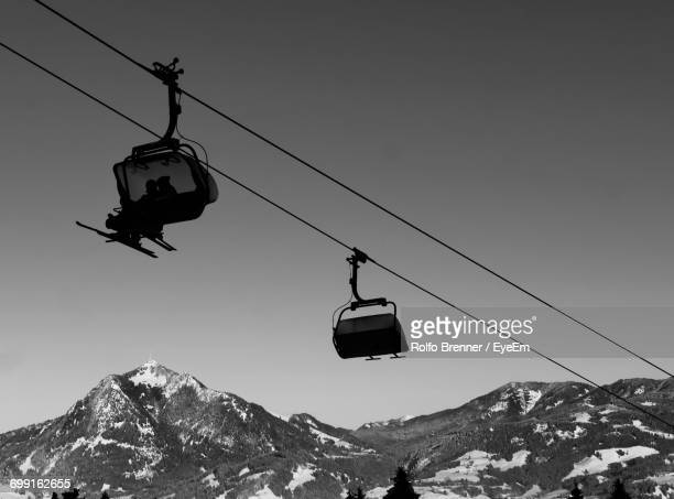 Low Angle View Of People Sitting On Ski Lift Against Clear Sky