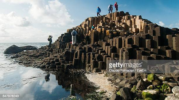 Low Angle View Of People Standing On Giants Causeway Against Sea