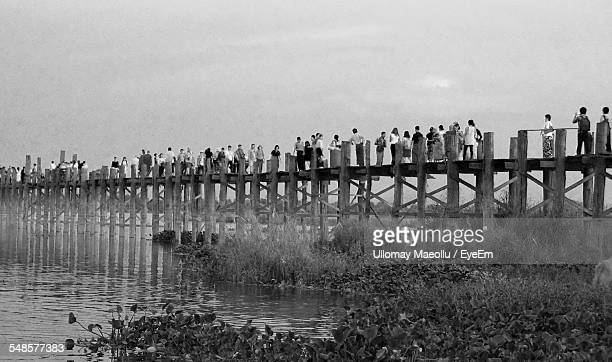 Low Angle View Of People Walking On Pier Over River