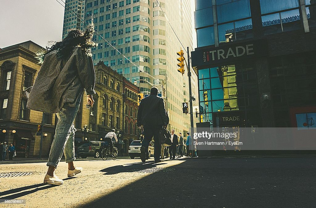 Low Angle View Of People Walking On Street Against Buildings In City