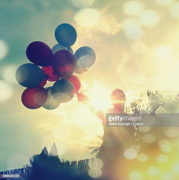 Low Angle View Of Person Holding Balloons Against Sky On Sunny Day