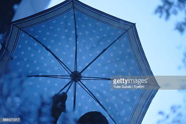 Low Angle View Of Person Holding Umbrella During Monsoon