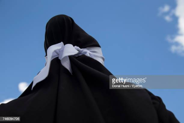 Low Angle View Of Person In Black Traditional Clothing Against Blue Sky