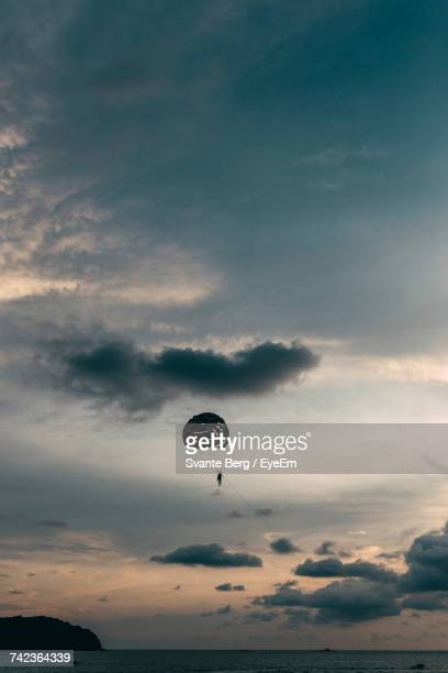 Low Angle View Of Person In Parachute Over Sea During Sunset Against Cloudy Sky