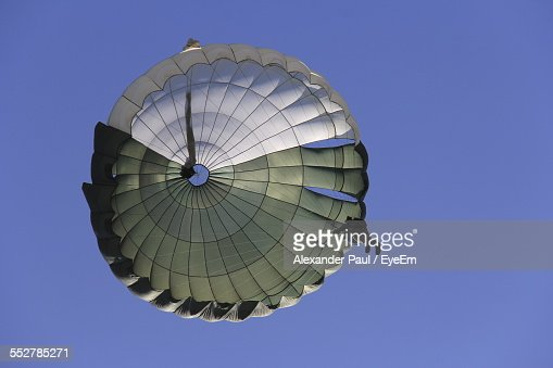 Low Angle View Of Person In Parachuting Against Clear Blue Sky