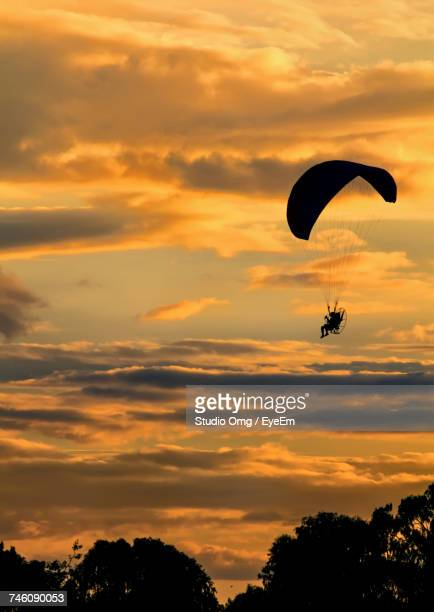 Low Angle View Of Person Powered Paragliding In Cloudy Sky During Sunset