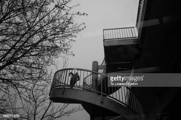 Low Angle View Of Person Running On Spiral Staircase Against Sky