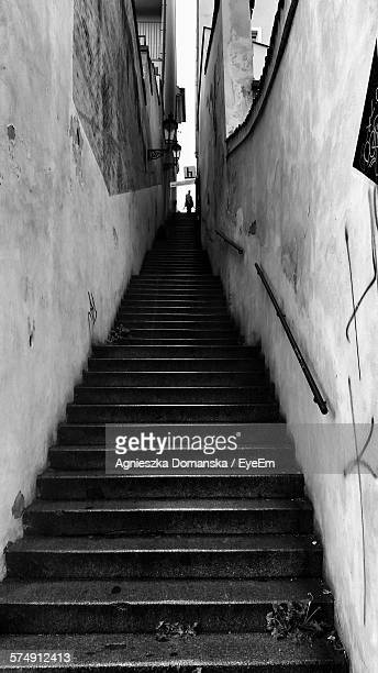 Low Angle View Of Person Standing On Top Of Narrow Staircase Amidst Buildings