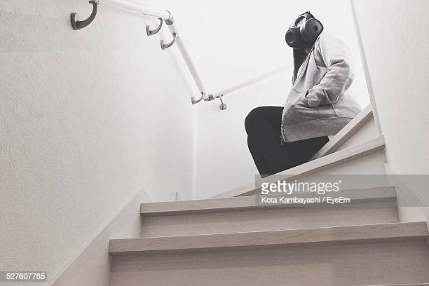 Low Angle View Of Person With Gas Mask Sitting On Steps