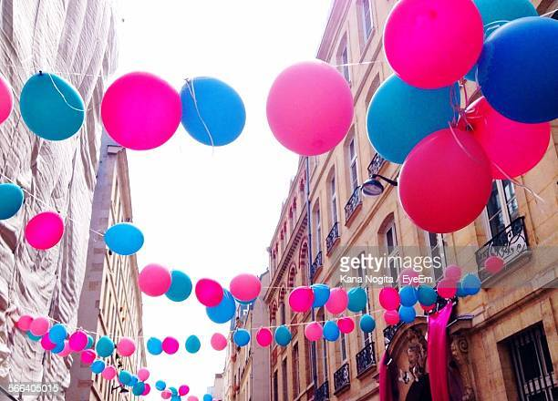 Low Angle View Of Pink And Blue Balloons Hanging Amidst Buildings During Festival