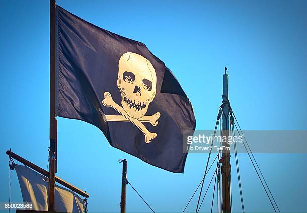 Low Angle View Of Pirate Flag On Boat Against Clear Sky