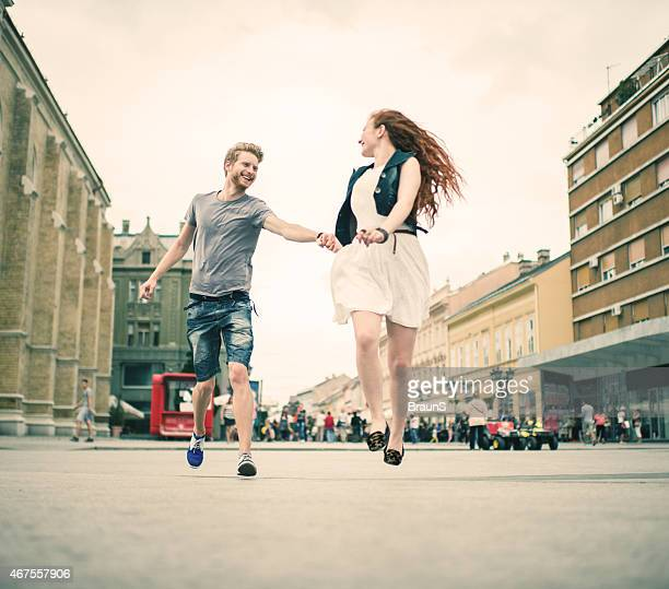 Low angle view of playful redhead couple in the street.