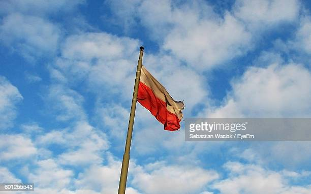 Low Angle View Of Polish Flag Against Cloudy Sky