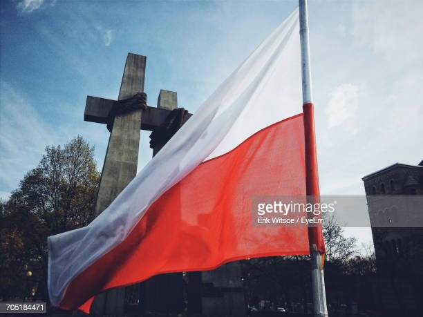 Low Angle View Of Polish Flag By Cross Against Sky In City
