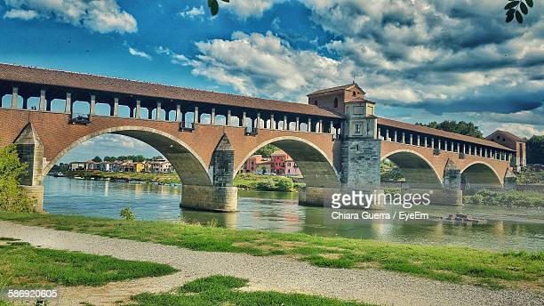 Low Angle View Of Ponte Vecchio Over River Against Cloudy Blue Sky