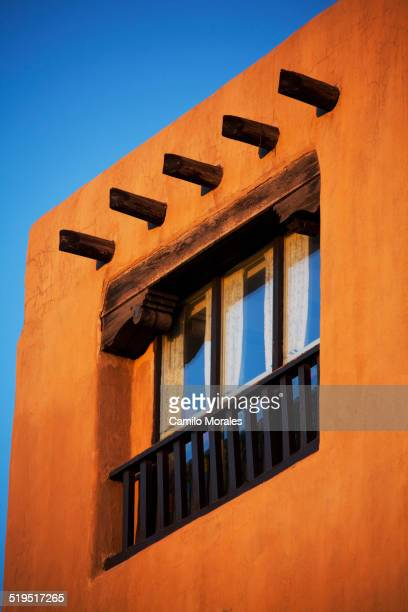 Low angle view of posts and window in adobe house