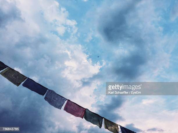 Low Angle View Of Prayer Flags Hanging Against Cloudy Sky