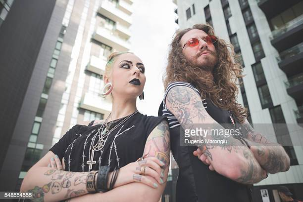 Low angle view of punk hippy couple with tattoos