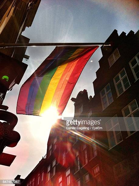 Low Angle View Of Rainbow Flag Hanging Amidst Buildings On Sunny Day
