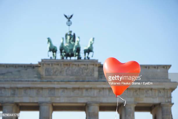 Low Angle View Of Red Heart Shape Balloon Against Brandenburg Gate