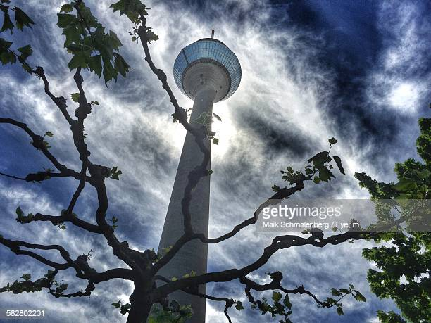Low Angle View Of Rheinturm Tower And Tree Against Cloudy Sky