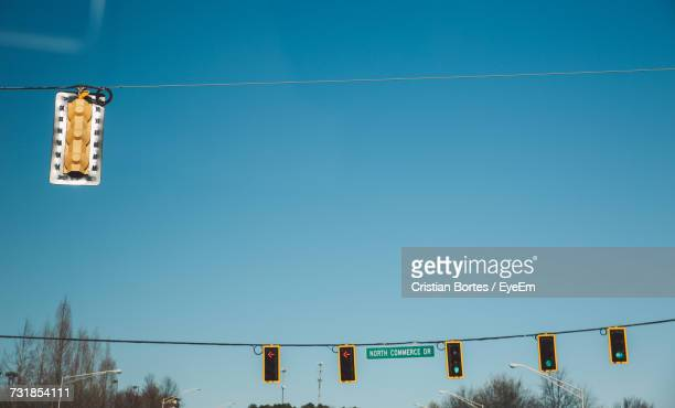Low Angle View Of Road Signals Hanging From Cables Against Sky