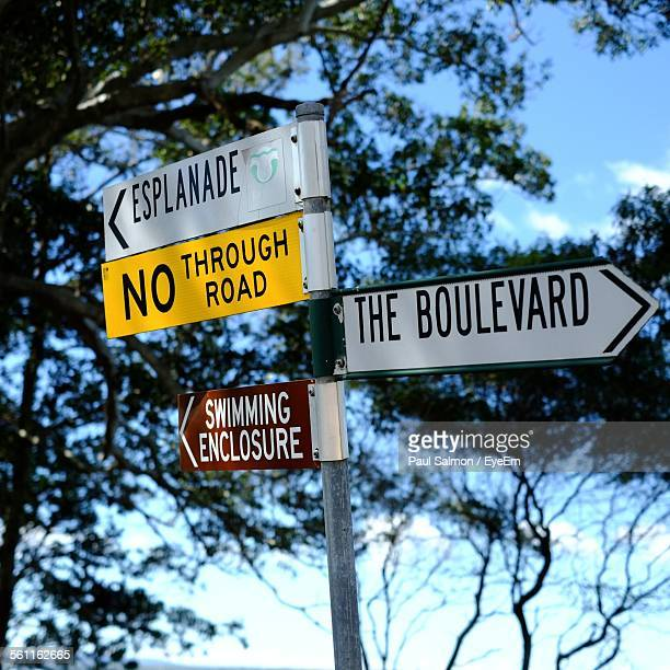 Low Angle View Of Road Signs Against Trees