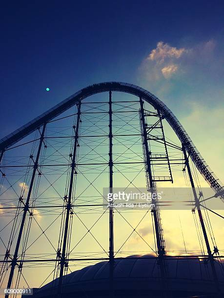 Low Angle View Of Rollercoaster Against Blue Sky On Sunny Day
