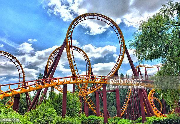 Low Angle View Of Rollercoaster Ride Against Cloudy Sky