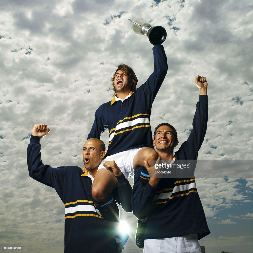low angle view of rugby players carrying their teammate on their shoulders and cheering : Stock Photo