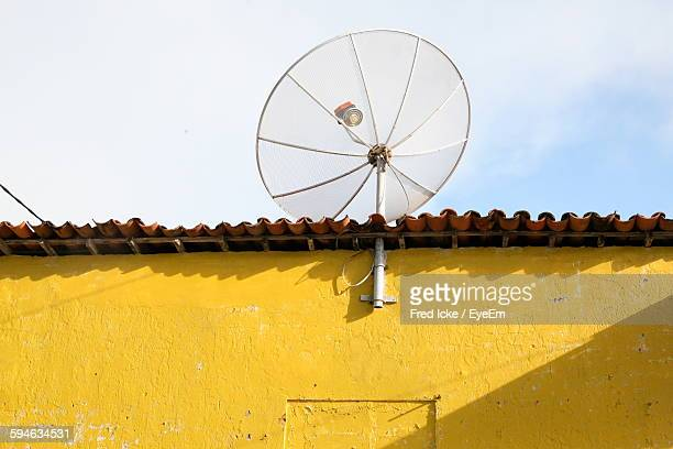 Low Angle View Of Satellite Dish On House Against Sky