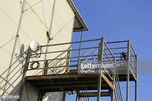 Low Angle View Of Satellite Dish On Metal Railing Against Blue Sky