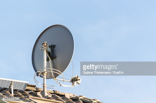 Low Angle View Of Satellite Dish On Roof Against Clear Sky