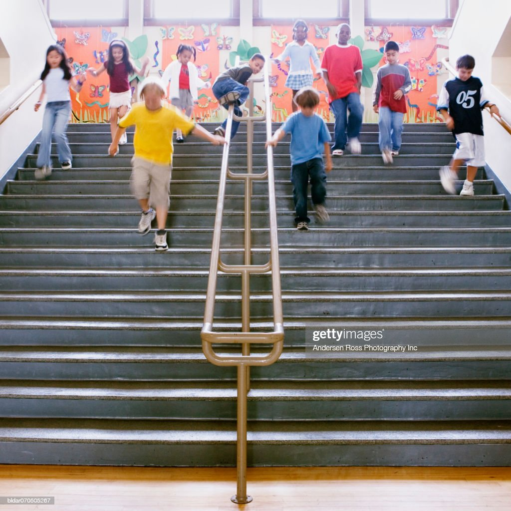 Low angle view of school children running down the stairs : Stock Photo
