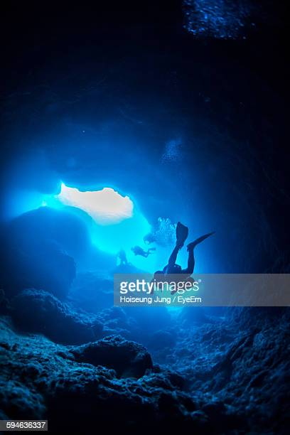 Low Angle View Of Scuba Divers Swimming In Cave