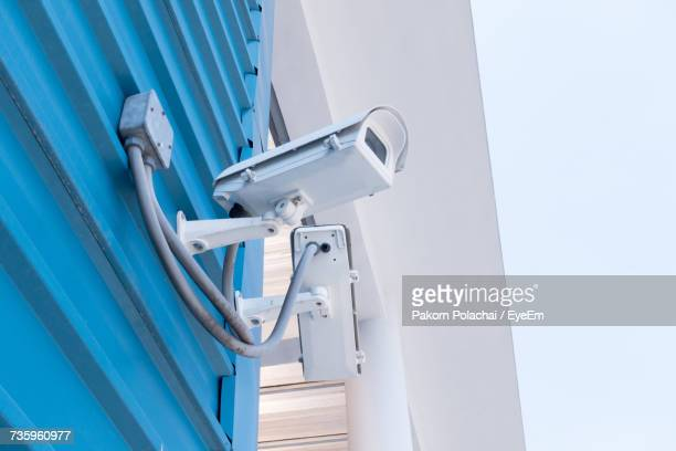 Low Angle View Of Security Camera Mounted On Wall