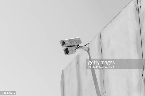 Low Angle View Of Security Camera On Wall Against Sky