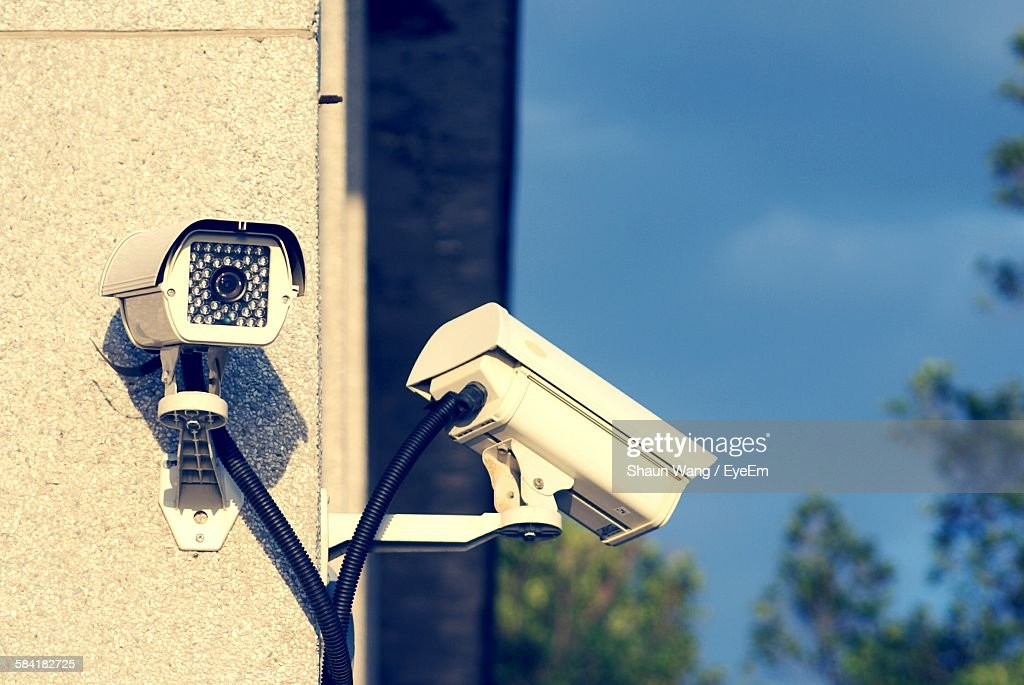 Low Angle View Of Security Cameras On Wall Against Sky