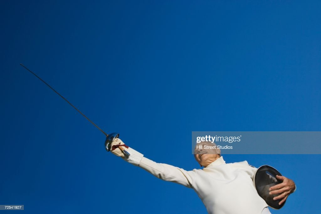 Low angle view of senior male fencer pointing epee : Stock Photo