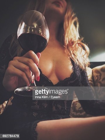 Low Angle View Of Sensuous Woman Holding Wineglass At Home