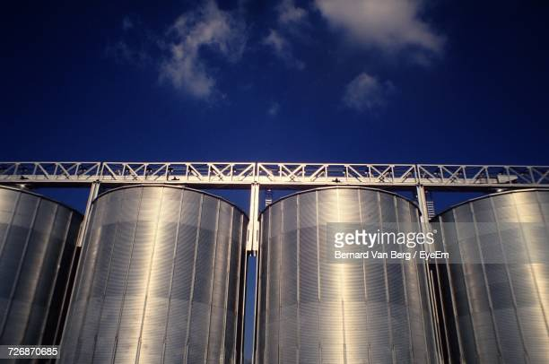 Low Angle View Of Shiny Silos Against Blue Sky